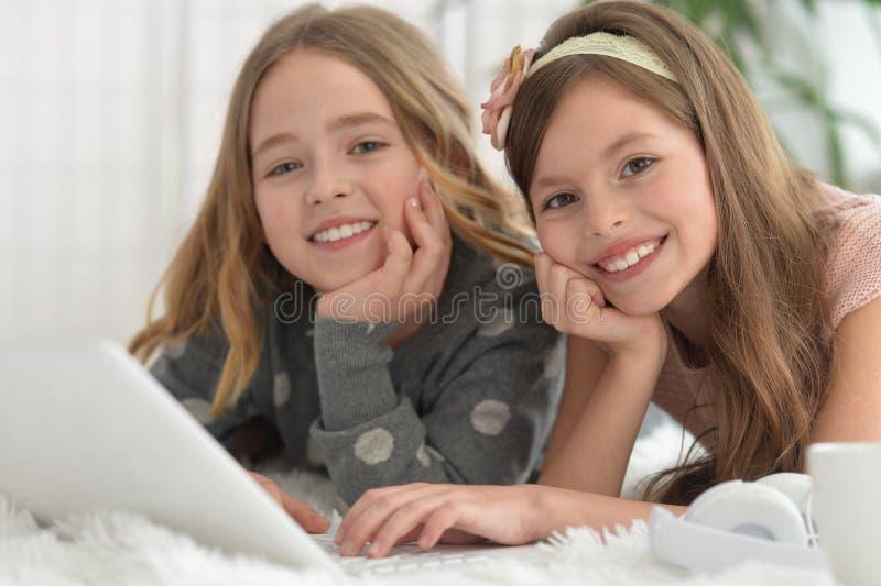 Le små flickor som använder en bärbar dator royaltyfria foton