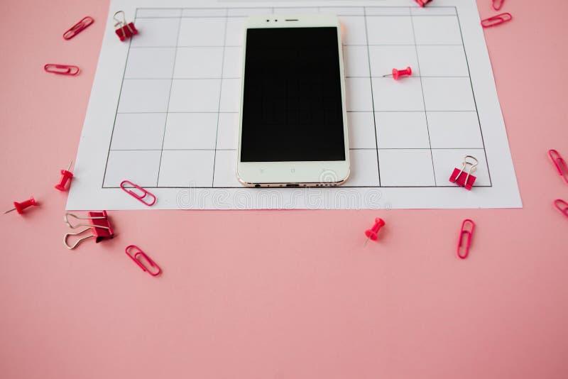 Le smartphone blanc se trouve sur un calendrier de papier Fond rose image stock
