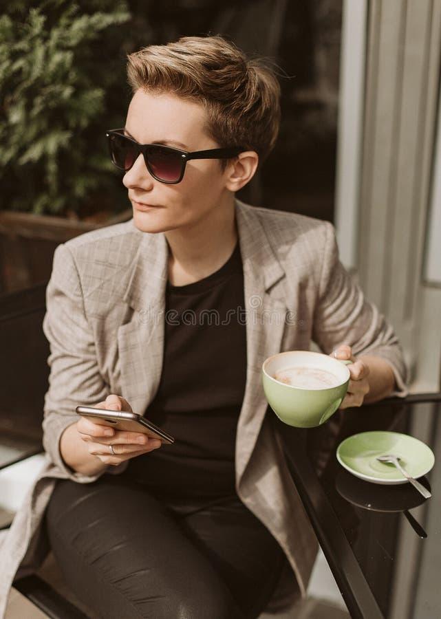 Le smartphone de style de femme d'affaires boit du café image stock