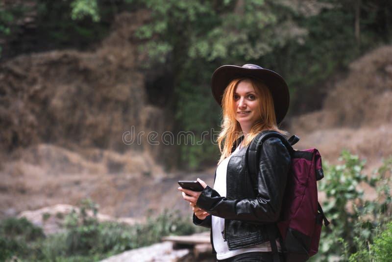 Le smartphone de touristes femelle d'utilisation, avec le sac à dos et le chapeau de cowboy regardant la rivière a enlevé le pont image stock