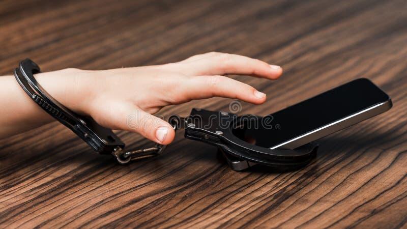 Le smartphone est menotté dans la main d'un petit garçon un symb photos libres de droits