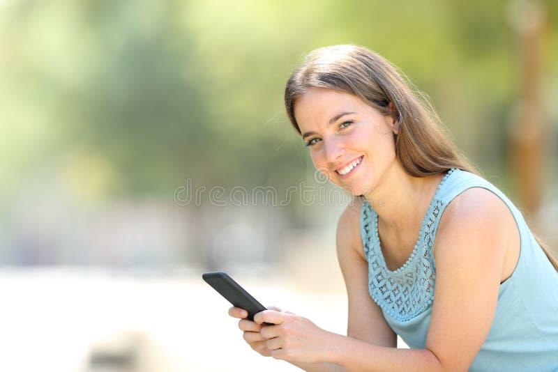 Le smartphone heureux de participation de femme regarde la caméra photos libres de droits