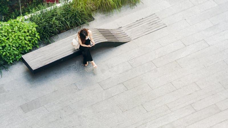 Le smartphone supérieur d'utilisations de femme de vue aérienne se reposent sur le banc en bois à wal images libres de droits