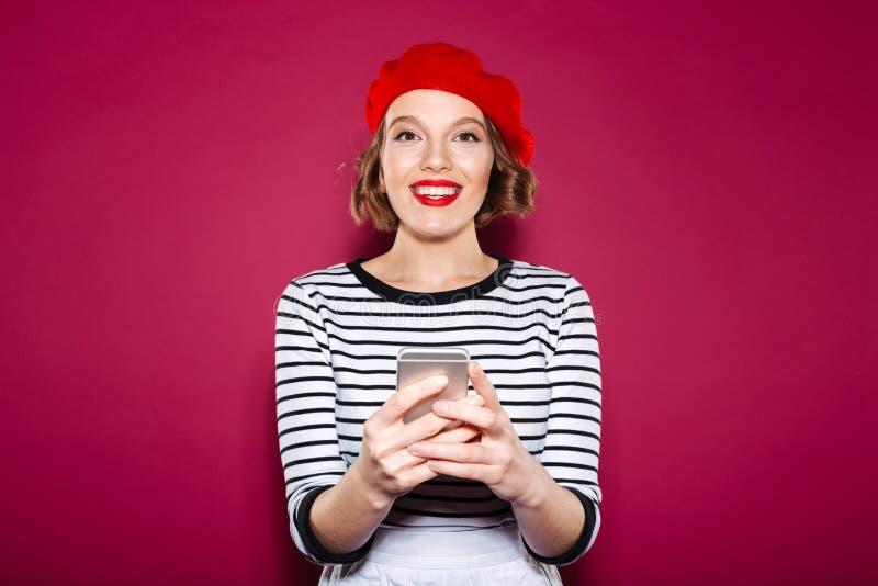Le smartphonen och att se för ljust rödbrun kvinna den hållande kameran royaltyfri foto