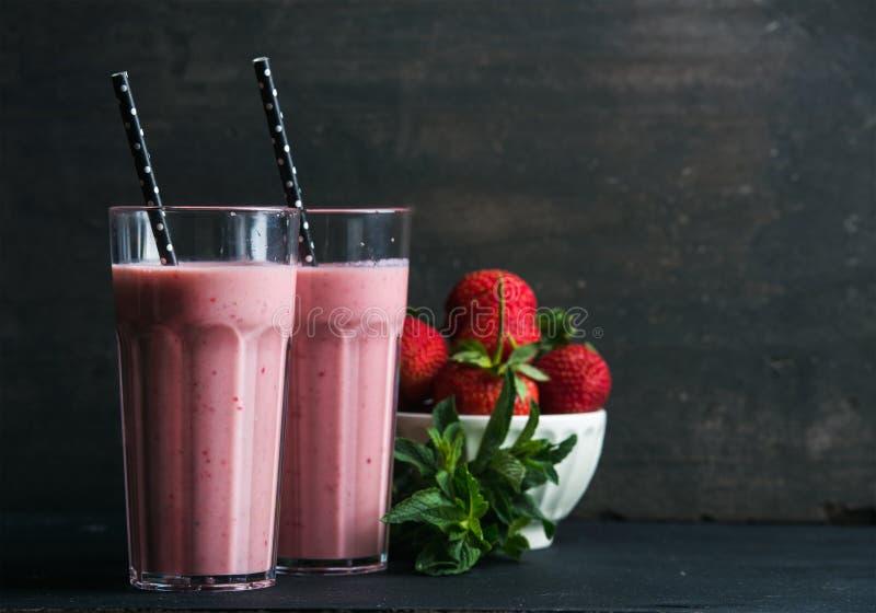 Le smoothie de fraise et de menthe en verres grands, braillent des baies fraîches sur le fond en bois rustique foncé photographie stock