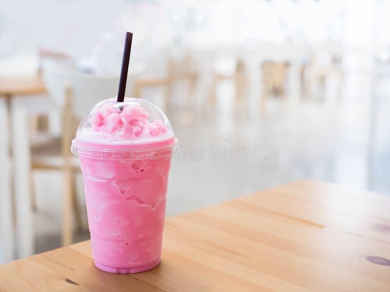 Le smoothie froid de lait dans une tasse en plastique sur une table en bois et a le su photos libres de droits