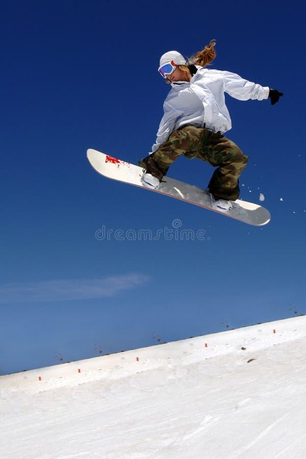 Le snowboarder de femme sautent la pente image stock