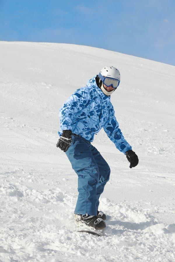 Le Snowboarder glisse vers le bas la pente neigeuse de ski photographie stock