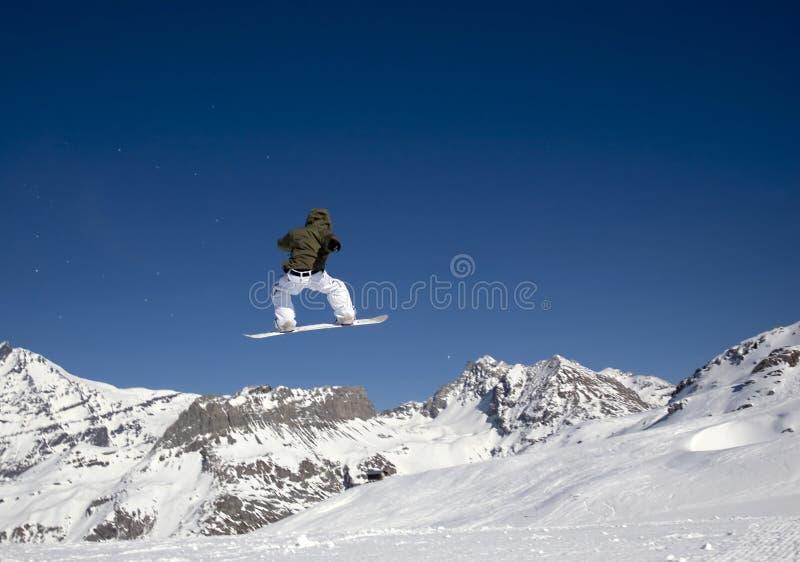 Le Snowboarder sautant haut dans le ciel photos stock