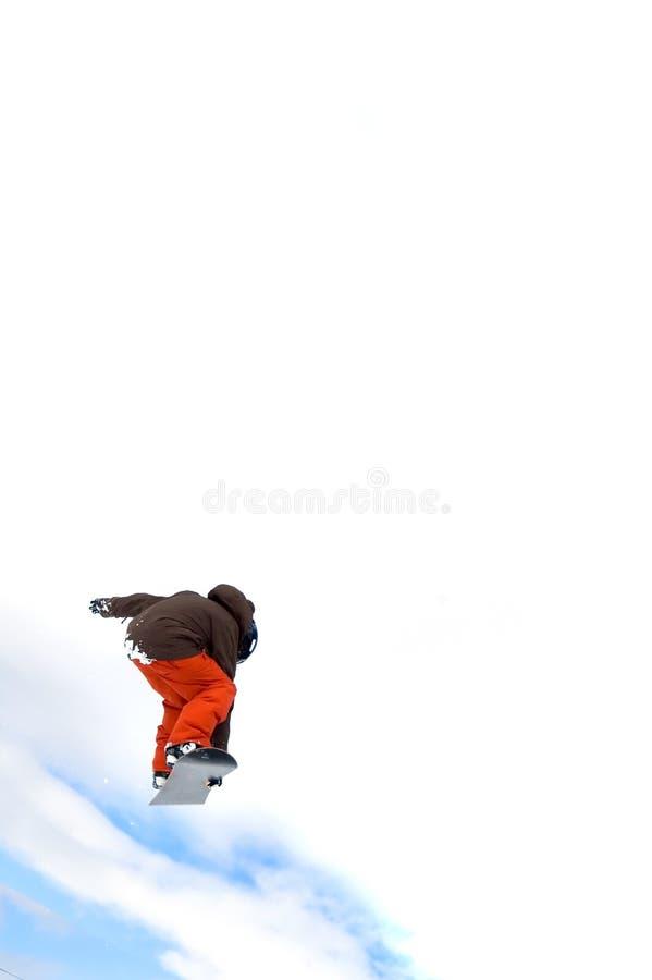 Le Snowboarder sautant haut dans le ciel image stock