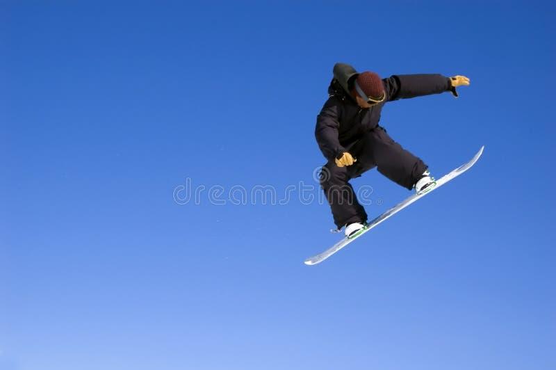 Le Snowboarder sautant haut dans le ciel images libres de droits