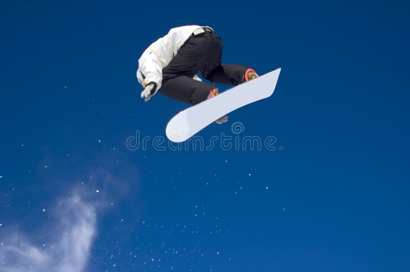 Le Snowboarder sautant haut dans le ciel photo stock
