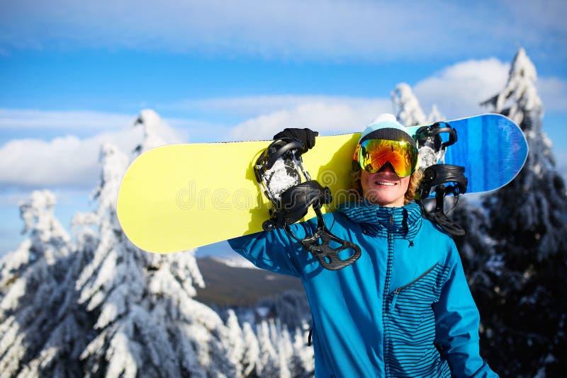 Le snowboarderen som poserar den bärande snowboarden på skuldra på, skida semesterorten nära skog för backcountry freeride och arkivbild