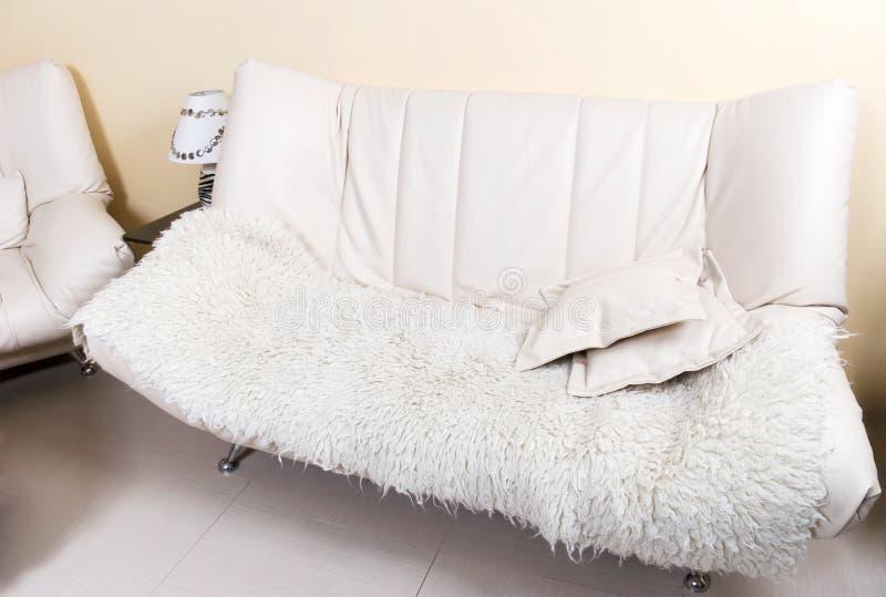 Le sofa moderne de cuir blanc avec est tombé photographie stock libre de droits