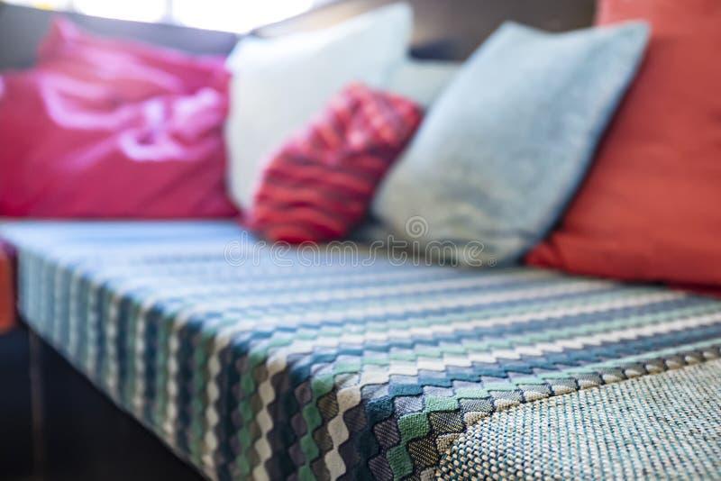 Le sofa mou et confortable est couvert de beau couvre-lit et d'oreillers de diff?rentes couleurs Int?rieur et confort dans photo libre de droits