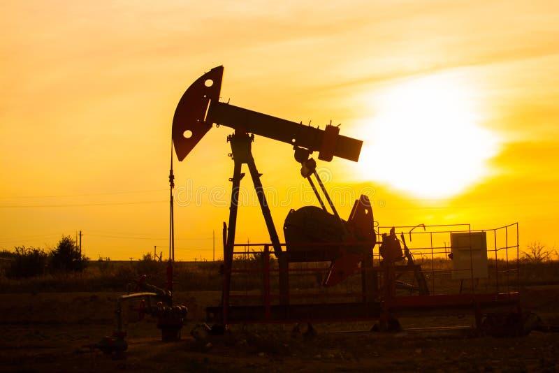 Le soir, le contour de la pompe à huile La pompe à huile, équipement industriel  Le site de gisement de pétrole, pompes à huile f photos libres de droits