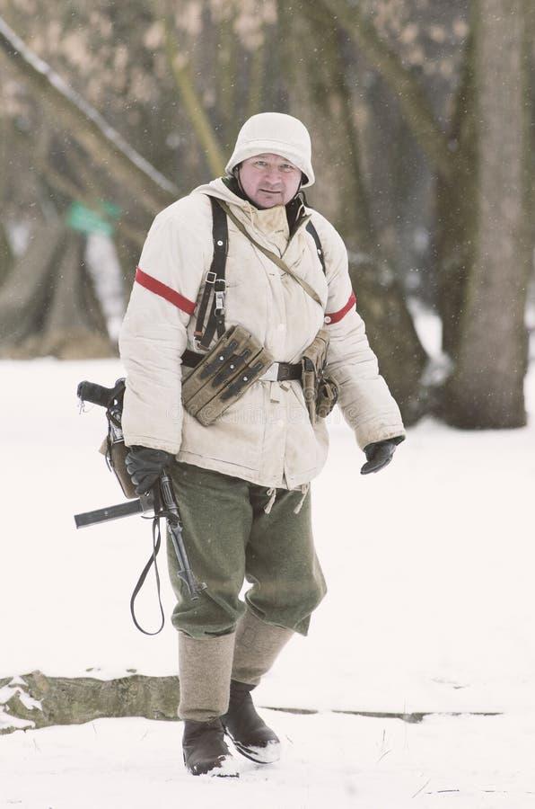 Le soldat allemand dans le camouflage d'hiver avec une arme à feu, MP-40 tient à disposition la position de fonctionnement photo libre de droits