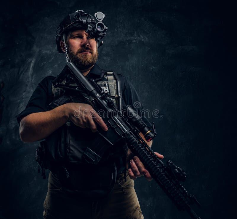 Le soldat barbu de forces spéciales ou l'entrepreneur militaire privé tenant un fusil d'assaut et observe les environs dedans image libre de droits
