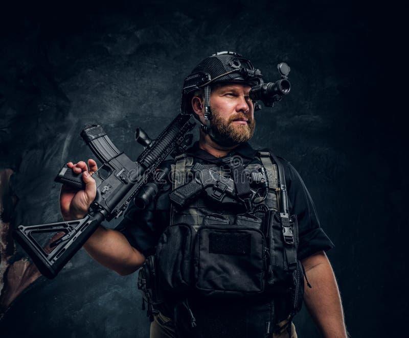 Le soldat barbu de forces spéciales ou l'entrepreneur militaire privé tenant un fusil d'assaut et observe les environs dedans photos libres de droits
