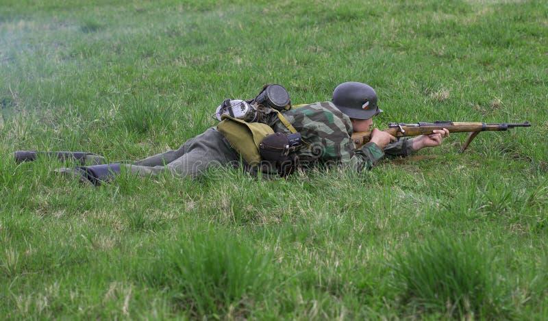 Le soldat d'infanterie allemand se situe dans l'herbe Reconstruction de l'épisode de la grande guerre patriotique photo libre de droits