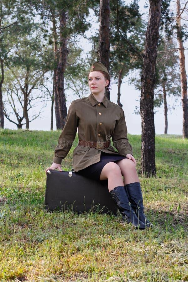 Le soldat féminin soviétique dans l'uniforme de la deuxième guerre mondiale s'assied sur une valise photo libre de droits