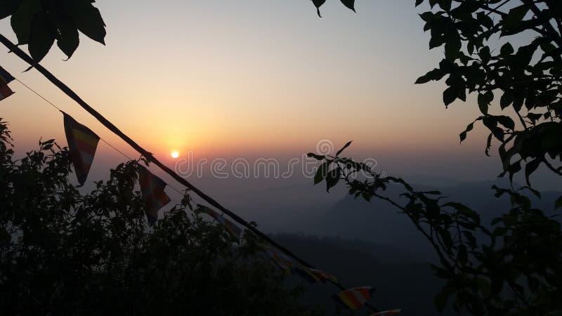 Le soleil apparaît sur le dessus de la colline de siripade avec l'empreinte de pas du Bouddha photo libre de droits