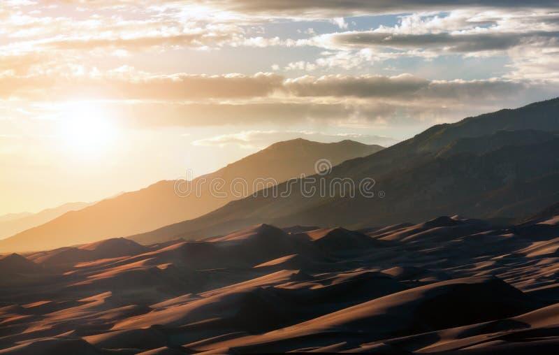 Le soleil brille au-dessus du parc national des Great Sand Dunes dans les montagnes Rocheuses du Colorado photos stock
