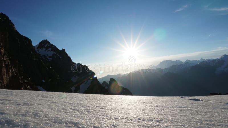 Le soleil brille brillamment Vue des montagnes neigeuses, du ciel bleu, de la falaise et des nuages blancs image stock