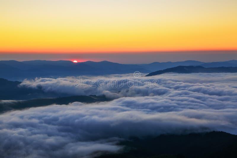 Le soleil d'écarlate à une aube, qui semble nager des crêtes de montagne, colorant le ciel illimité aux nuances oranges photographie stock libre de droits