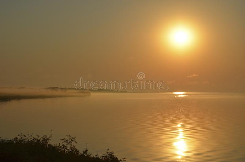 Le soleil d'été au-dessus du lac brumeux Fond mou image stock