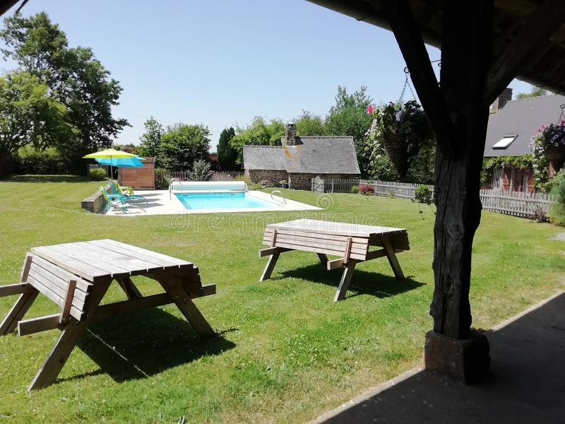 Le soleil d'été sur une piscine et des tables de pique-nique image stock