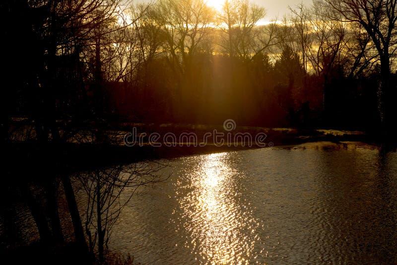 Le soleil d'or d'hiver traversant des nuages image stock