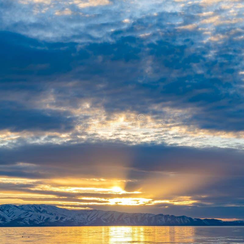 Le soleil d'or de cadre carré brillant par le ciel nuageux et a réfléchi sur le lac brillant ci-dessous images stock