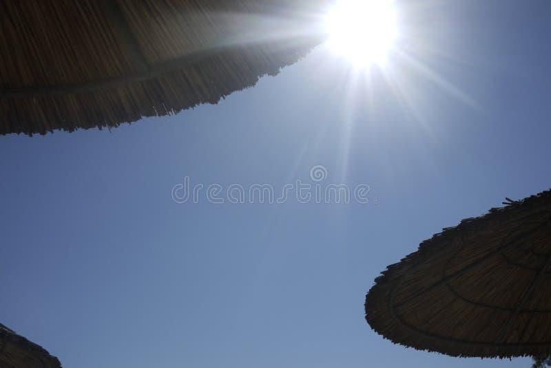 Le soleil de Brighton de parapluies de paille de plage a éclaté en ciel bleu photographie stock