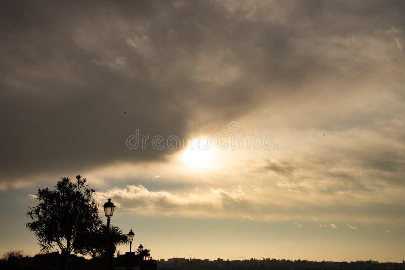 Le soleil de coucher du soleil avec la silhouette des arbres, des réverbères et des oiseaux photographie stock