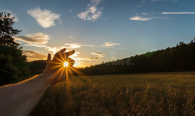 Le soleil de crochet de main d'homme au coucher du soleil sur le champ avec la forêt et le ciel Horizontal tch?que photo libre de droits