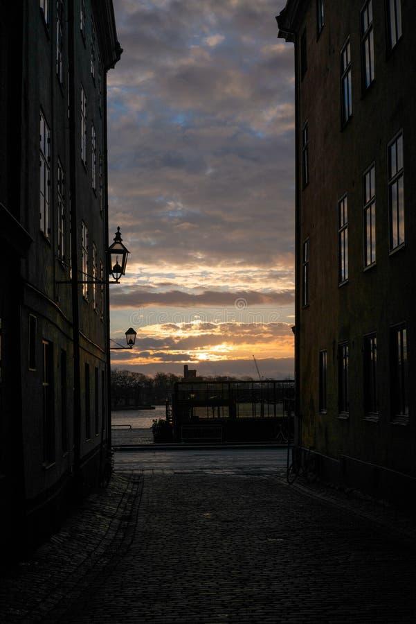 Le soleil de lever de soleil filtrant sur la vieille rue étroite pavée en cailloutis avec les maisons colorées à Stockholm pendan image stock