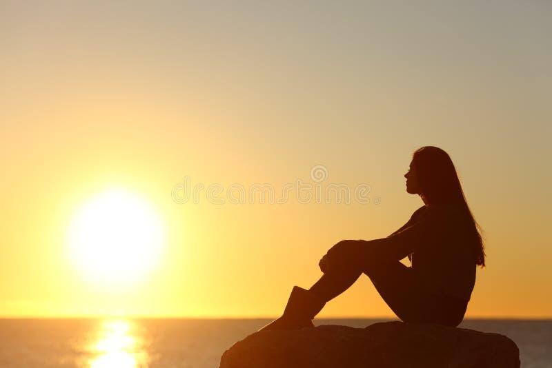 Le soleil de observation de silhouette de femme dans un coucher du soleil photographie stock libre de droits