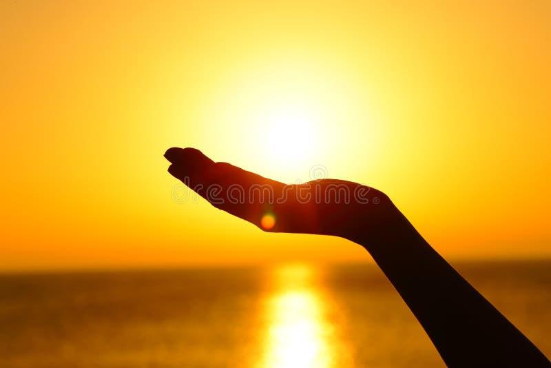 Le soleil de participation de main de femme au coucher du soleil sur la plage image stock