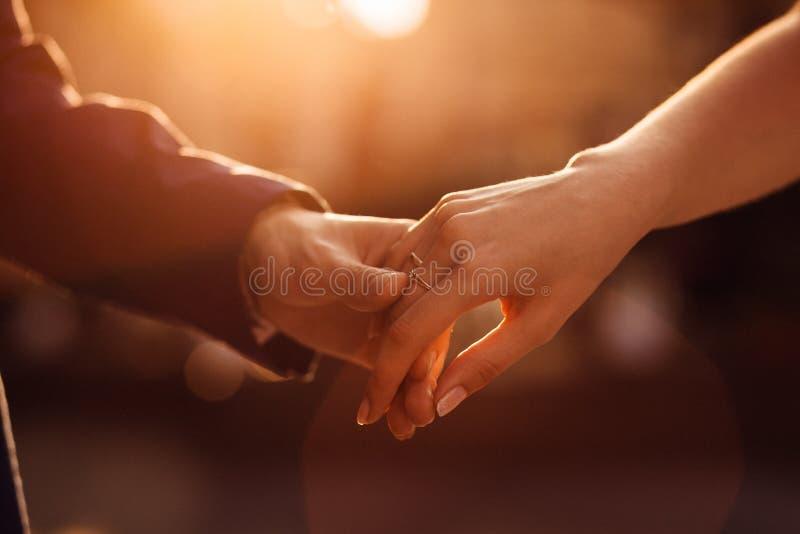 Le soleil de soirée brille au-dessus du newlyweds& x27 ; se tenant tightl image stock