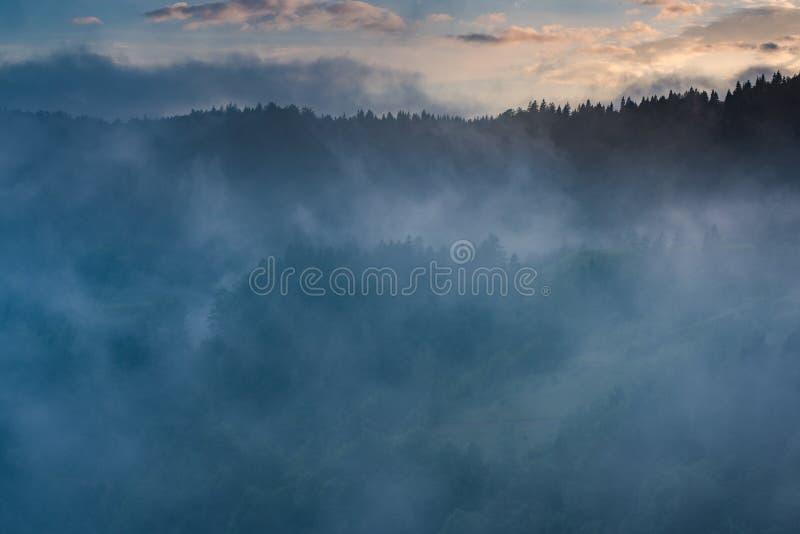 Le soleil de soirée rayonne traverser les nuages et le brouillard en montagne photographie stock