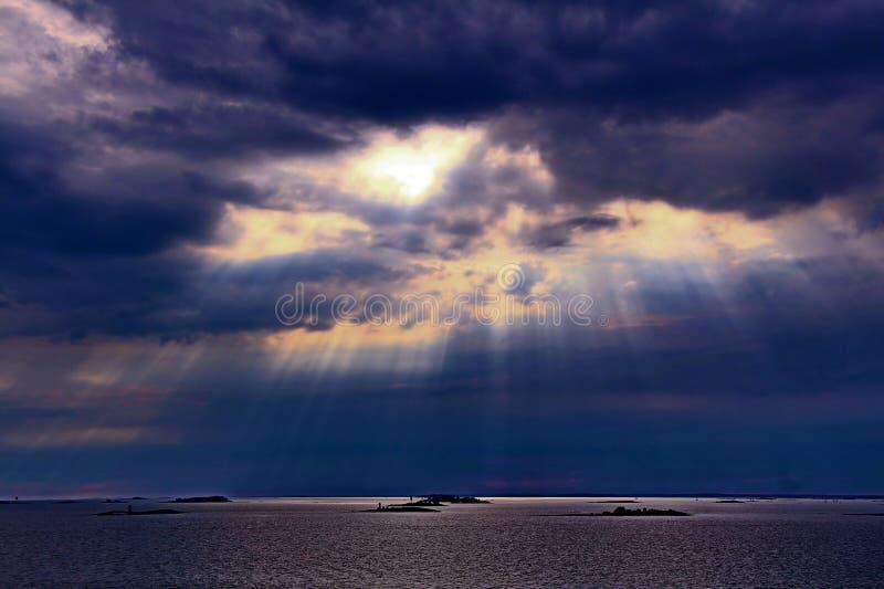 Le soleil derrière les nuages avec des rayons de bas brillant léger sur la mer photos libres de droits