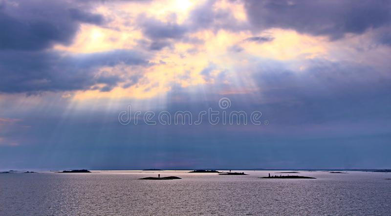 Le soleil derrière les nuages avec des rayons de bas brillant léger sur la mer photographie stock