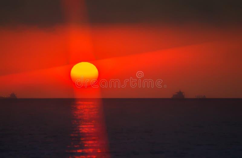 Le soleil ensanglanté entre la mer et le nuage images stock