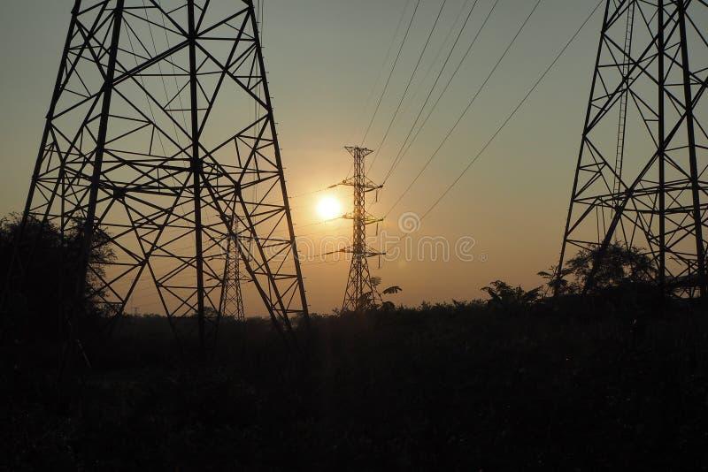 Le soleil est près de l'horizon Lumière par le pylône à haute tension images libres de droits