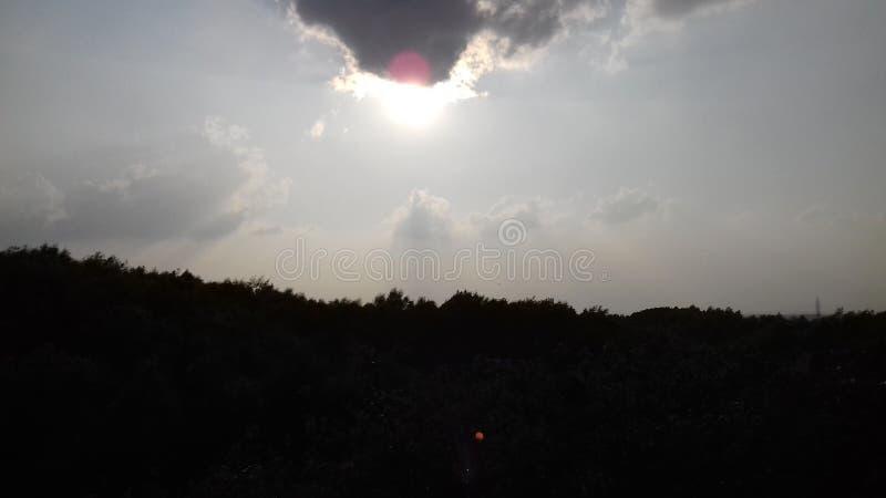 Le soleil fâché au-dessus de la colline verdâtre photographie stock libre de droits
