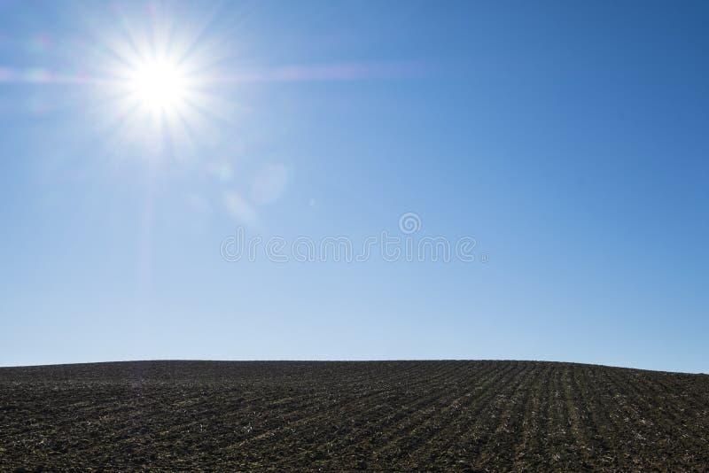 Le soleil lumineux brille sur le champ labouré avec un ciel bleu clair image libre de droits