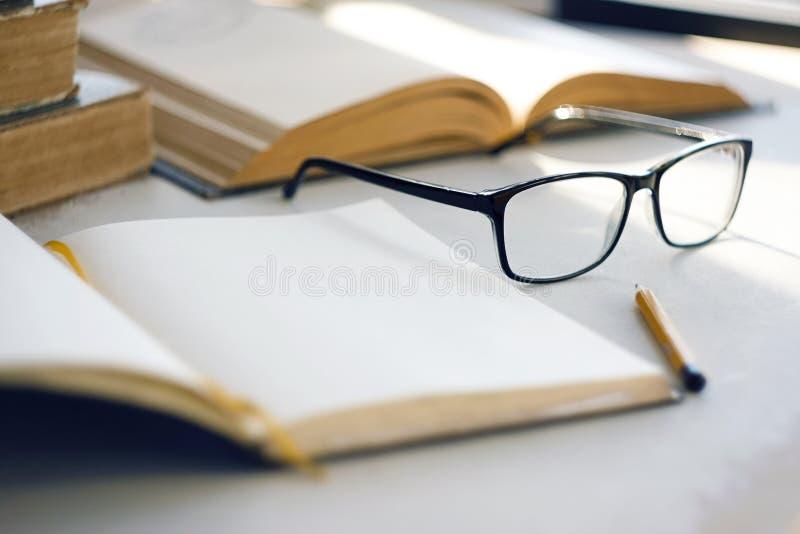 Le soleil lumineux illumine de vieilles encyclopédies, un carnet, un crayon simple et des verres image stock