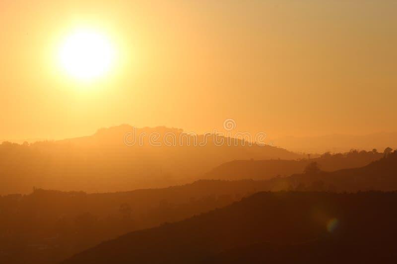 Le soleil lumineux parmi des silhouettes des montagnes image stock