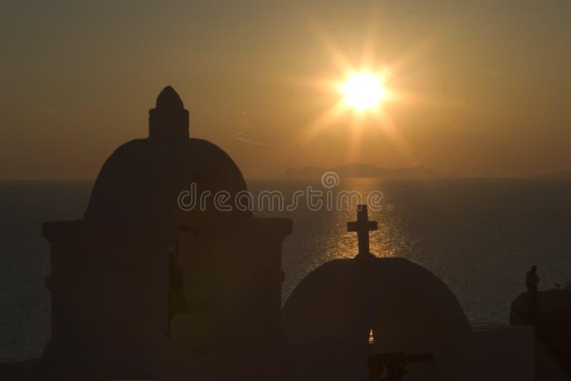 Le soleil place derrière une des nombreuses églises orthodoxes dans la ville de Fira, Santorini photos stock